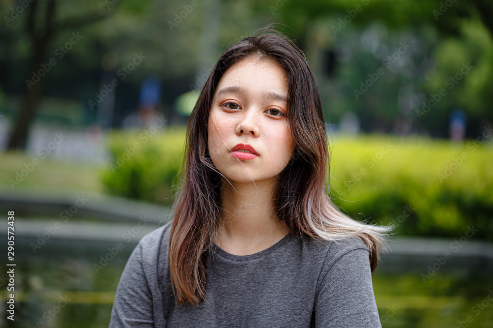 Portrait of Chinese Teenager. Asian Appearance. Calm, sad face. Cute Girl looking at the camera, a close up portrait in the park.