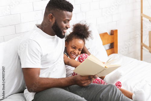 Loving african american dad reading fairy tales to his little daughter Wallpaper Mural