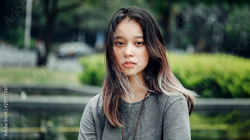 Fototapety, obrazy: Portrait of Chinese Teenager. Asian Appearance. Calm, sad face. Cute Girl looking at the camera, a close up portrait in the park. Copy space.