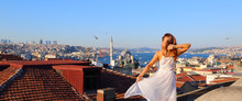 Happy Young Woman Standing On The Rooftop In Istanbul Turkey. Back View Of The Girl In White Long Dress At The Famous Tourist Attraction Of Istanbul. Travel, Tourism, Excursions.