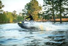 Teenage Boy Man Driving A Personal Watercraft Outside On A Lake Pond At Sunset