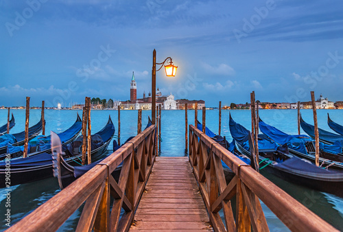 Fotomural Evening Venice seascape with gondolas at moorings, light of lantern at wooden bridge, view at famous San Giorgio Maggiore island with basilica and campanile from Piazza San Marco