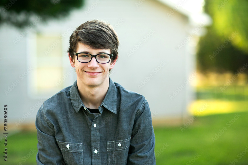 Fototapety, obrazy: Teenage Boy with Glasses Outside on a spring day sitting outside of a house home smiling