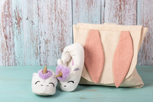 Baby Girl Backpack And Fluffy Slippers Composition On Rustic Wooden Background