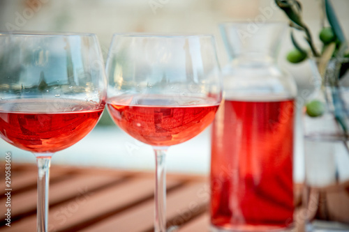 Cadres-photo bureau Pain two glasses of rose wine with olives against blue water on a pier..