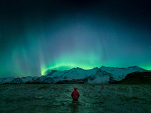 Person Wearing Red Hoodie Standing In Front Of Northern Lights