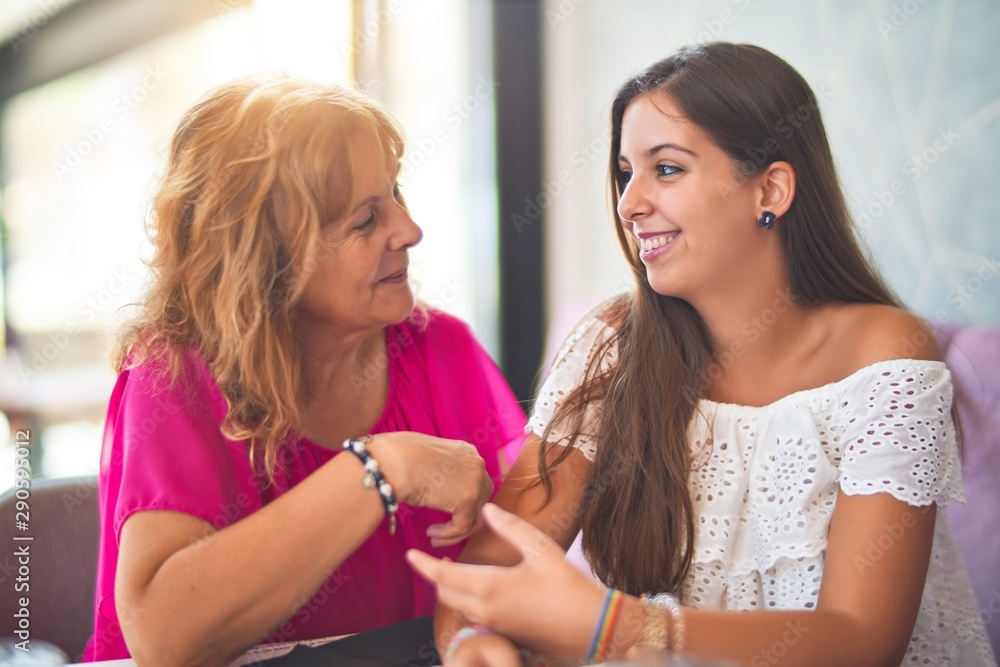 Fototapeta Beautiful mother and daugther sitting at restaurant speaking and smiling