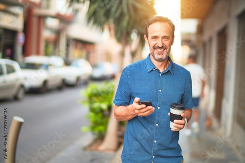 Fototapety, obrazy: Middle age handsome businessman standing on the street using smartphone drinking take away coffee smiling
