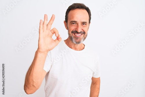 Fotografía  Middle age handsome man wearing casual t-shirt standing over isolated white background smiling positive doing ok sign with hand and fingers
