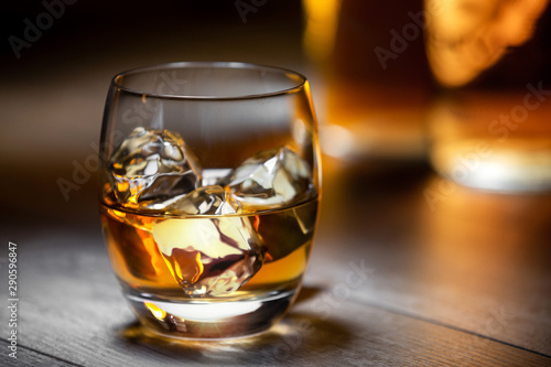 Canvas Elegant and refreshing glass of scotch bourbon whisky on ice with glowing illumi