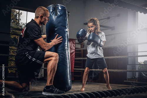 Experienced boxer trainer is training new little girl boxer for special competitions using punching bag Wallpaper Mural