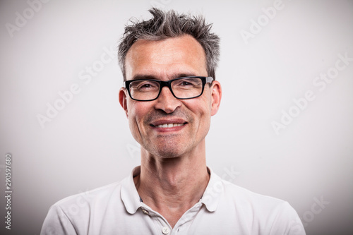 Canvastavla  smart middle aged grayed man with unkempt hair and black designer glasses makes