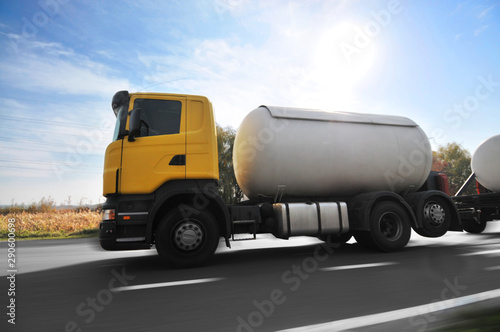 Fotomural Big metal fuel tanker truck shipping fuel on the countryside road in motion agai