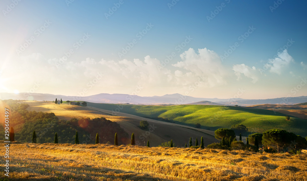 Fototapeta sunset over autumn Tuscany countryside landscape; rolling hills and village