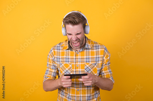 Involved in gaming. Get music subscription. Man satisfied listen music modern headphones and smartphone. Best music apps that deserve listen. Guy modern user mobile application. Fresh music concept - 290602244