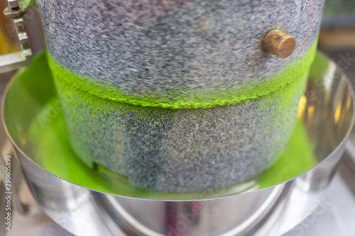 Matcha green tea grinding stone machine in motion with vibrant colorful powder i Fototapeta