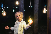 Cute Adorable Caucasian Blond Girl Portrait Smiling And Holding In Hand One Of Hanged Edison Light Bulb At Forest Outdoor. Right Solution Choice Concept