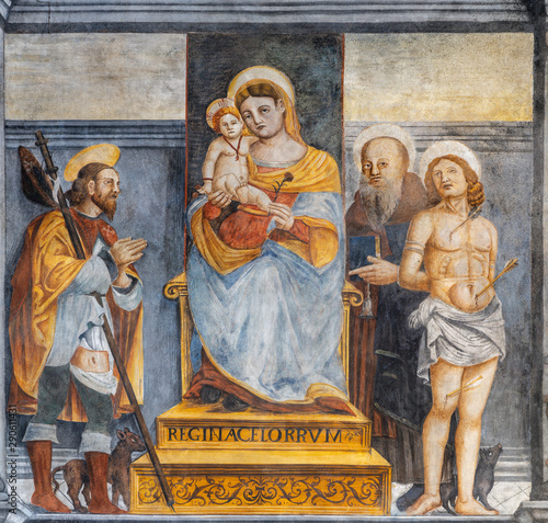 LIMONE SUL GARDA, ITALY - MAY 9, 2015: The freso of Madonna with the saints Roch, Sebastian and probably Benedict in the church San Rocco.