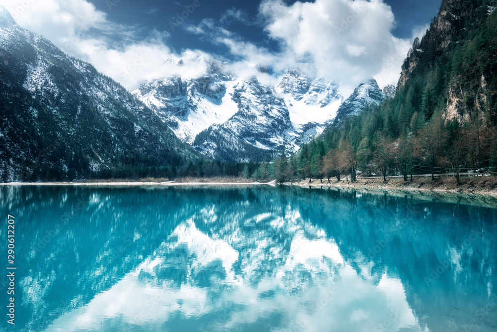 Fototapeta Mountain lake with perfect reflection at sunny day in autumn. Dolomites, Italy. Beautiful landscape with azure water, trees, snowy mountains in clouds, blue sky in fall.  Snow covered rocks. Nature