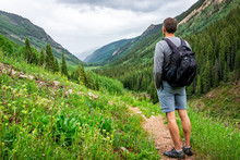 Man Looking At Valley View On Conundrum Creek Trail In Aspen, Colorado In 2019 Summer With Green Lush Grass On Cloudy Day And Dirt Road