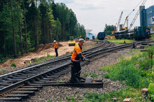 Workers On Railway And Freight Train Transporting Large Diameter Pipes