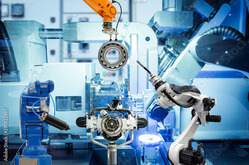Fotografia  Industrial automation robotic teamwork working with auto parts on smart factory, on machine blue tone color background, industry 4