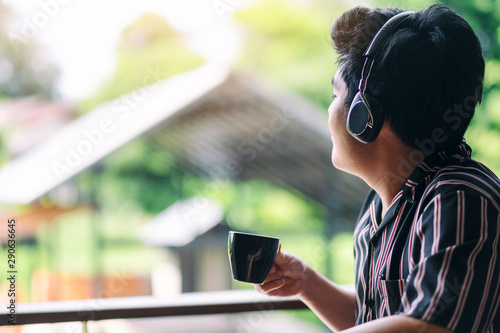 An asian man enjoy listening to music with headphone while drinking coffee - 290636645