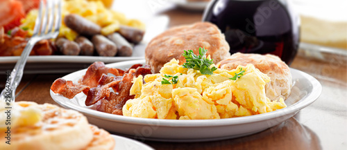 Photo  huge breakfast plate with scrambled eggs, bacon and biscuits