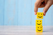 Leinwandbild Motiv smile face on yellow wood cube. Service rating, ranking, customer review, satisfaction and emotion concept.