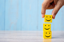 Smile Face On Yellow Wood Cube. Service Rating, Ranking, Customer Review, Satisfaction And Emotion Concept.