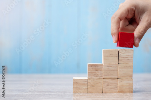 Fotografía  Businessman hand placing or pulling Red wooden block on the building