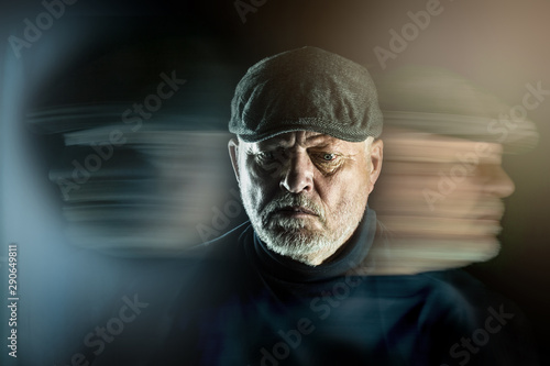 Obraz Portrait of a senior man with flat cap in front of black background. Ghostly faces surround him. Concept: surreal portrait - fototapety do salonu