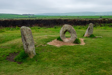 A Unique Rock Structure That Looks Like The Numbers 101 Overlooks The Green English Countryside On This Cloudy Day.