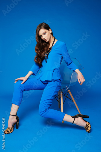 High fashion portrait of young elegant woman. Blue blouse, blue pants, curly hair, leopard shoes. . Wall mural