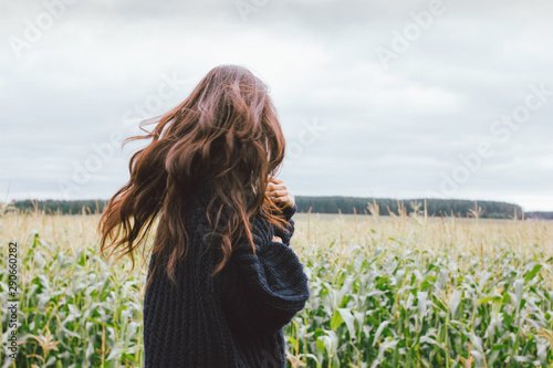 Stampa su Tela  Beautiful carefree windy long hair girl in knitted sweater in the autumn corn field
