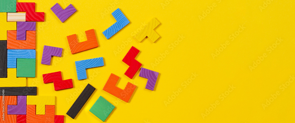 Fototapeta Different colorful shapes wooden blocks on yellow banner background. Top view