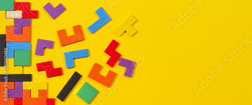 Different colorful shapes wooden blocks on yellow banner background Wallpaper Mural