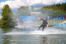 Man Wakeboarding On Lake Behind Boat. Water Skiing