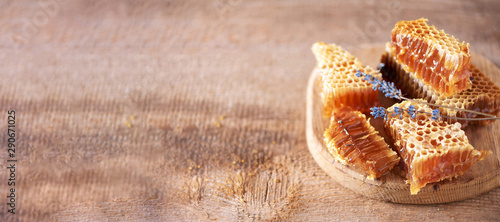Fresh honeycombs pieces, dry lavender flowers on wooden background Wallpaper Mural