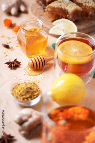 Alternative medicine concept. Ingredients for flu fighting natural hot drink. Copy space. Lemon, ginger, mint, honey, apple and spices on craft paper background
