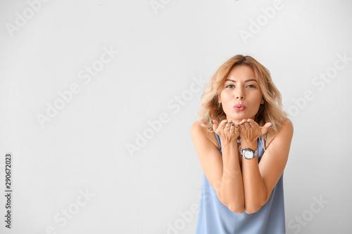 Obraz Portrait of beautiful woman blowing kiss against light background - fototapety do salonu