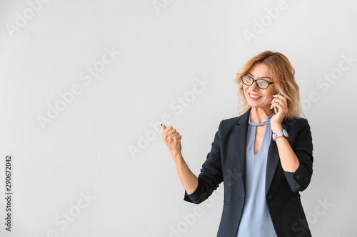 Pinturas sobre lienzo  Portrait of beautiful businesswoman talking by phone on light background