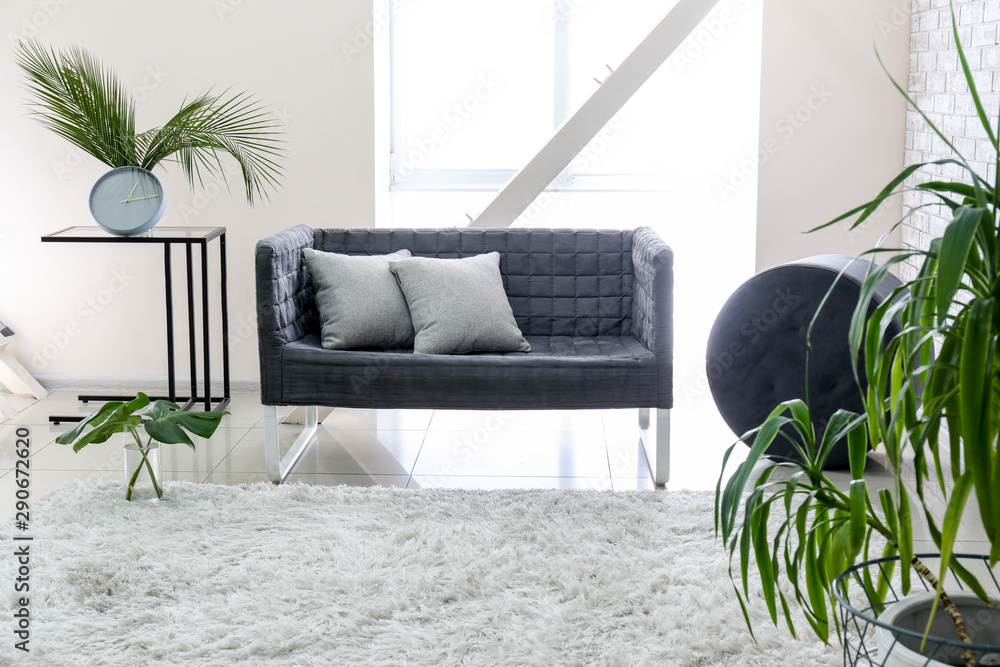 Fototapeta Interior of modern room with sofa and floral decor