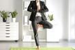 Leinwanddruck Bild - Young businesswoman practicing yoga in office