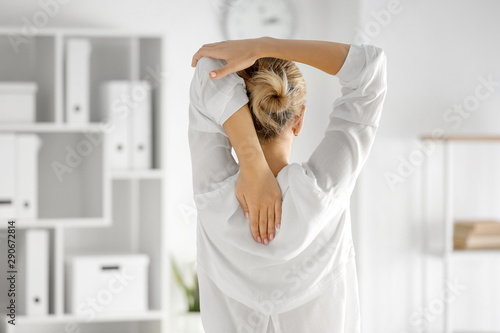 Cuadros en Lienzo Young businesswoman practicing yoga in office, back view