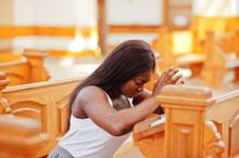 African American Woman Praying In The Church. Believers Meditates In The Cathedral And Spiritual Time Of Prayer. Afro Girl Folded Hands While Sitting On Bench.