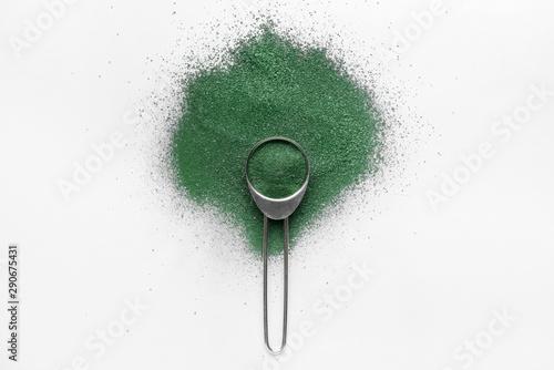 Photo Scoop with spirulina powder on light background