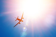 canvas print picture Bright sun in the sky and a flying passenger plane in height. The concept of tourism, vacation, travel.