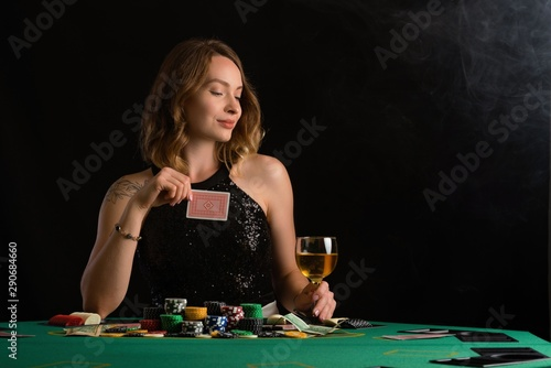 A young girl in a black evening dress plays poker in a casino Wallpaper Mural