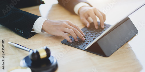 Lawyer working on a laptop and providing legal document for his client